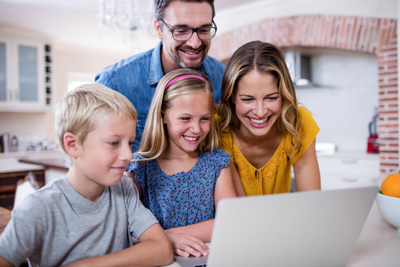 Parents and kids using laptop in kitchen
